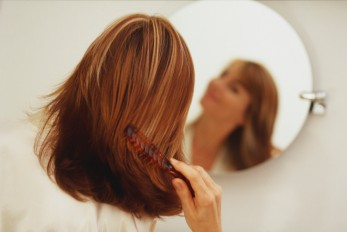 women running a comb through her hair as she looks in the mirror