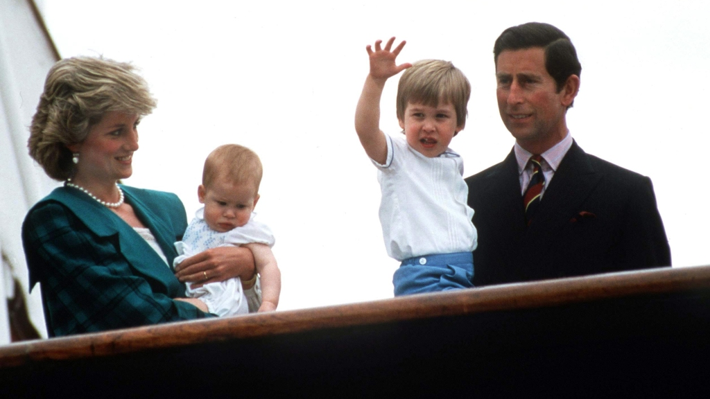 Princess Diana holding baby Prince Harry next to Prince Charles holding young Prince William