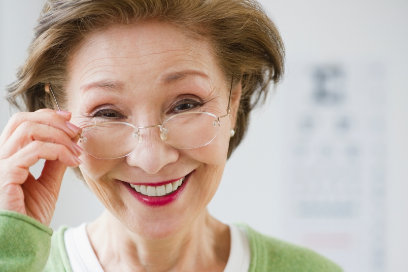 older woman holding her glasses and smiling
