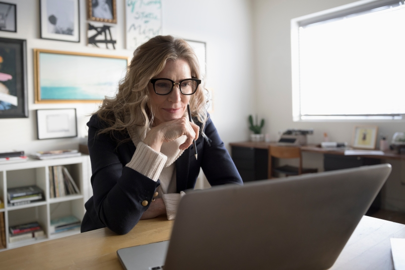women wearing glasses stares at a computer screen while concentrating