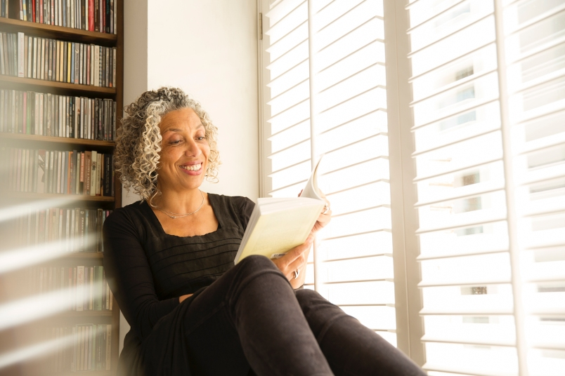 older black woman reading a book while leaning against a bookshelf