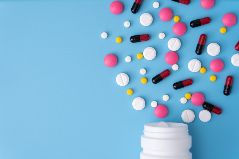 High Angle View Of Pills Spilling Form Bottle On Blue Background