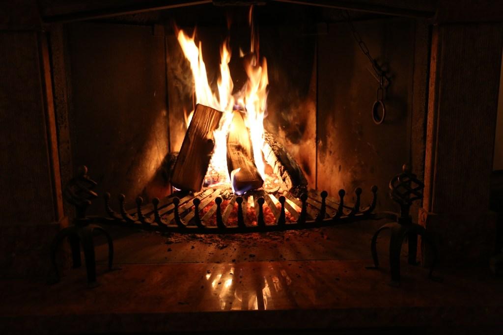 Burning Fireplace In Darkroom At Night