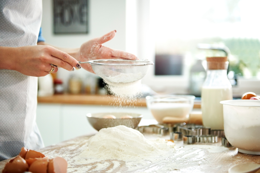 Woman sifting flour in kitchen