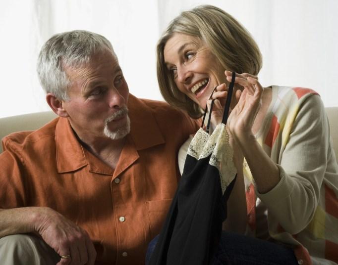 Senior woman holding a dress and looking at a senior man