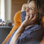 Smiling woman at home on cell phone with husband in background