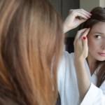 redhead woman examining hair near her scalp in a mirror