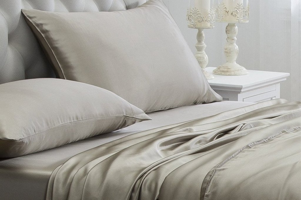 silk champagne colored sheet set displayed on a bed
