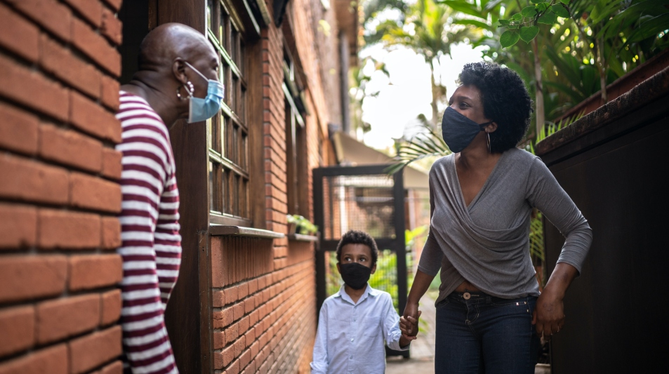Daughter visiting mother at home during pandemic using surgical mask