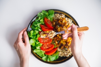 Top view of Female hands at dinner table holding fork above plate with quinoa, red beans, corn, tomato and green salad