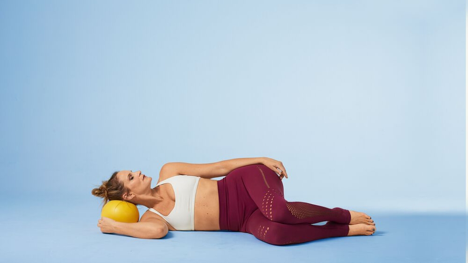 woman lying on side with a ball underneath her head