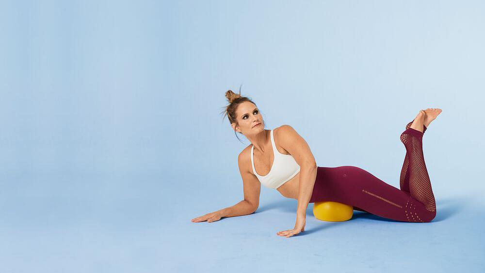 woman laying on massage ball massaging lower hip