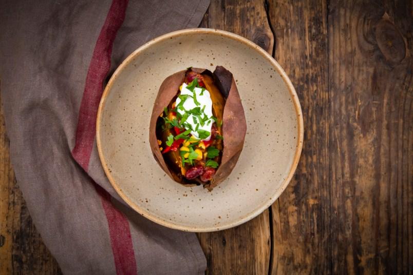 Sweet potato kumpir with chili con carne, sour cream and coriander