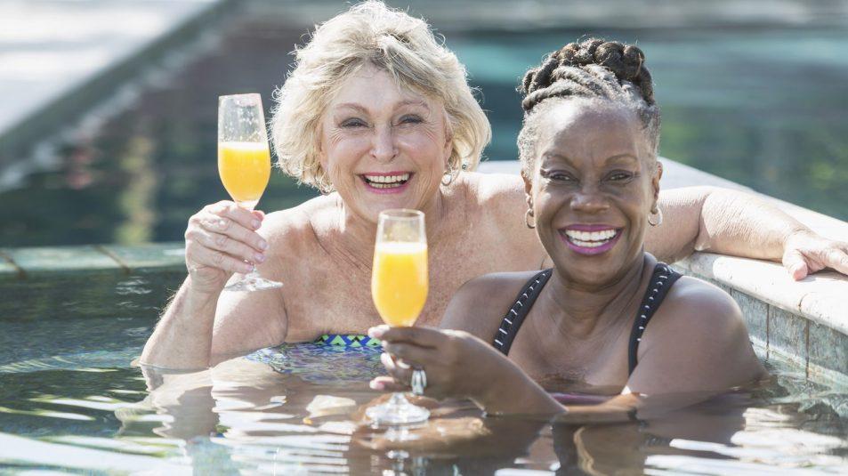Two mature women enjoying cocktail in swimming pool