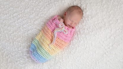 Newborn Baby Girl in a Rainbow Colored Pouch