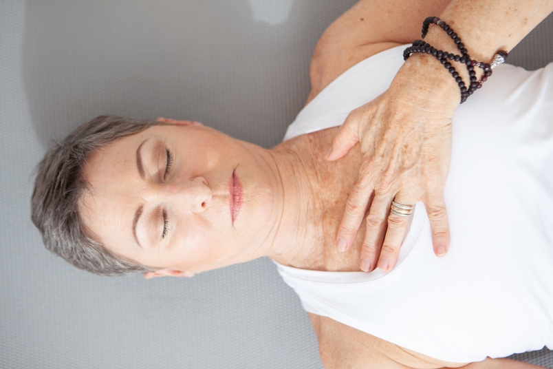 mature woman lying down on her back with eyes closed and hand on chest