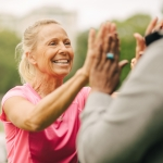 Happy senior woman giving high-five to female friend in park