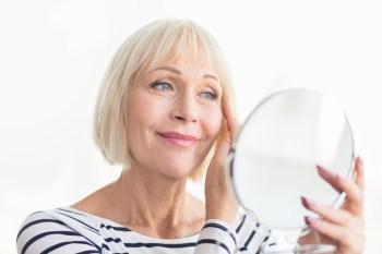 Senior woman touching her soft face skin