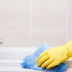 Gloved hand scrubbing bath tub
