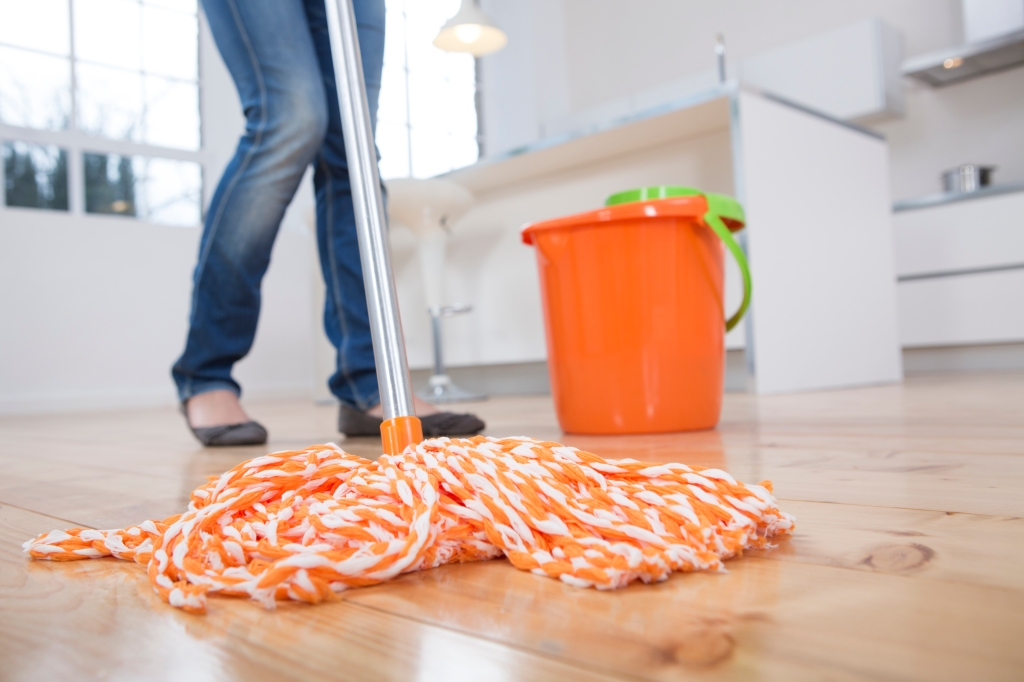 Woman mopping kitchen floor, low section