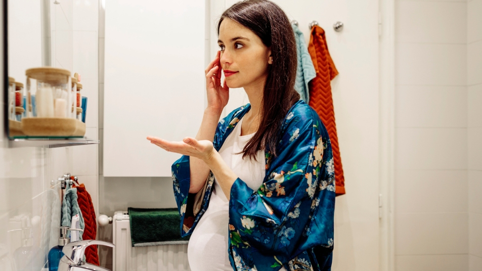 Pregnant woman putting on makeup