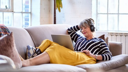 woman listening to headphones looking at computer