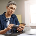Shot of a senior woman using a credit and mobile while working on her finances at home