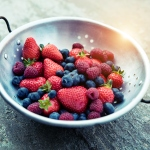 Strawberries, blueberries and raspberries in colander