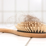 Hair loss in hairbrush on white tiles