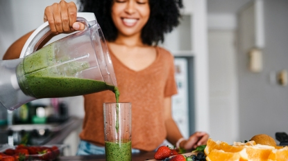 Smiling woman pouring smoothie