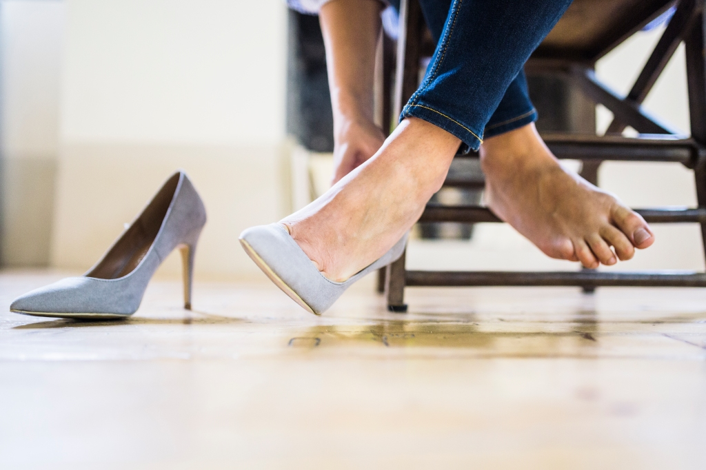 Woman taking off shoes at desk