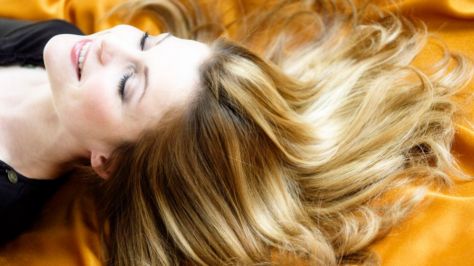 Portrait of a young woman lying, long hair on yellow textile fabric