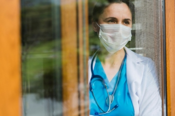 Female doctor looking through window at hospital with face mask on