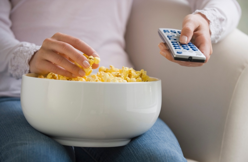 Close up of woman with remote control and bowl of popcorn