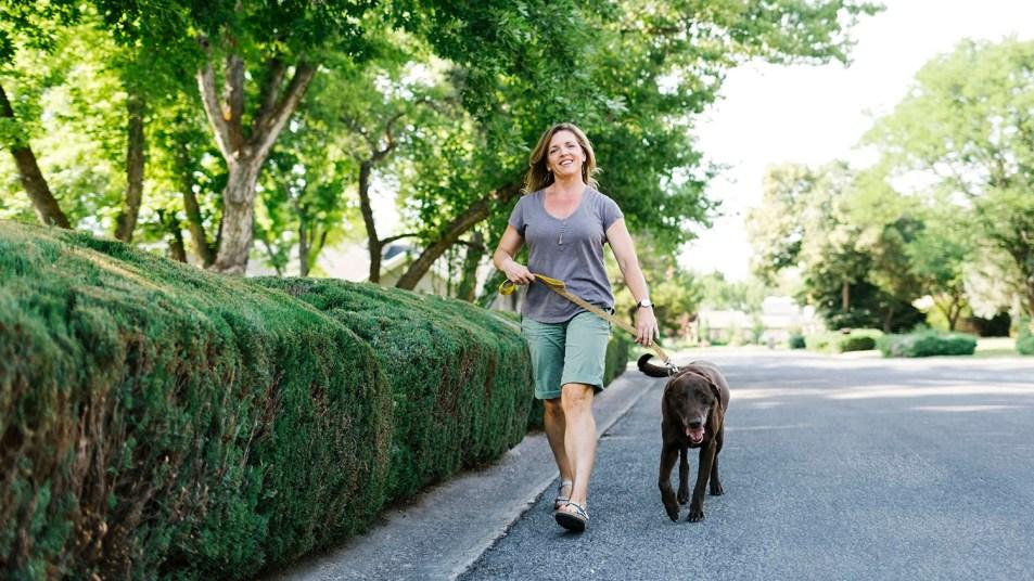 Woman walking with Labrador Retriever
