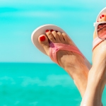 Woman's feet in sandals by the ocean