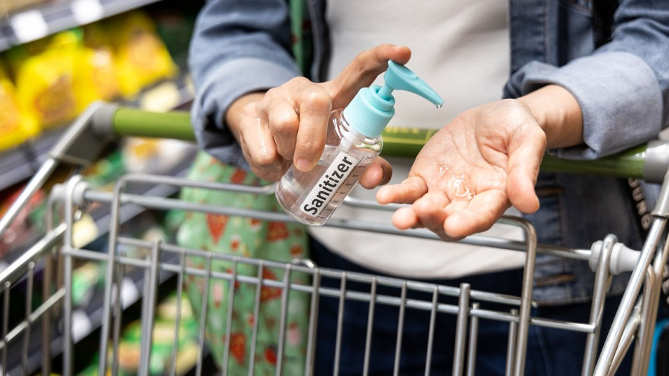Shopper disinfecting hands with sanitizer in supermarket during shopping