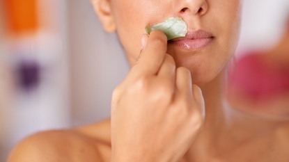 woman removing facial hair from upper lip