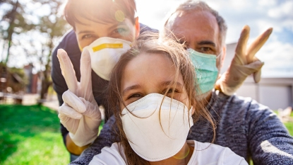 family outdoors wearing face masks taking selfie