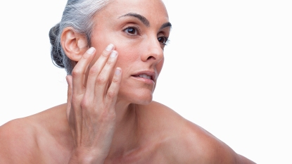 woman putting night cream on her face