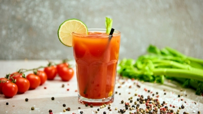 Glass of tomato juice surrounded by tomatoes, celery, and peppercorns