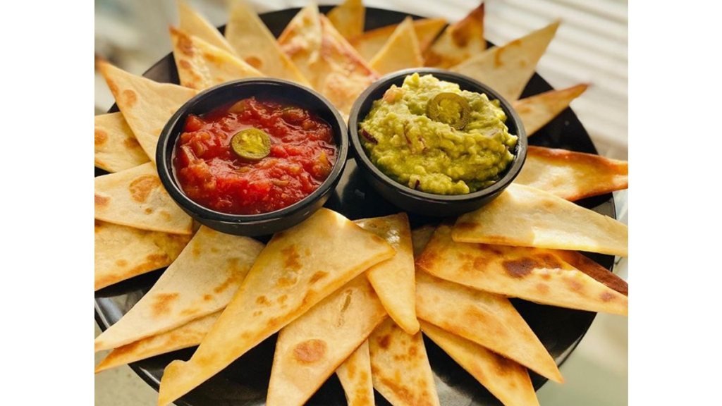 Plate of homemade tortilla chips with salsa and guacamole