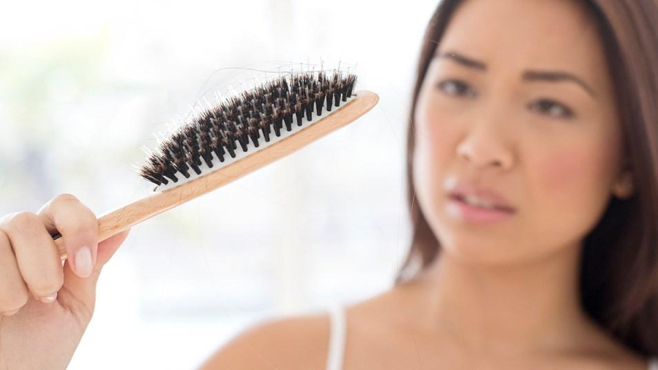 Woman looking at hair in hair brush