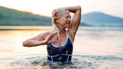 Woman touching her hair swimming in a lake