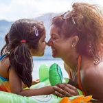 Mom with young daughter in a floatie swimming in a lake surrounded by nature
