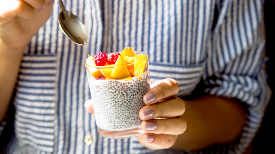 Woman's hands holding cup of yogurt with chia seeds