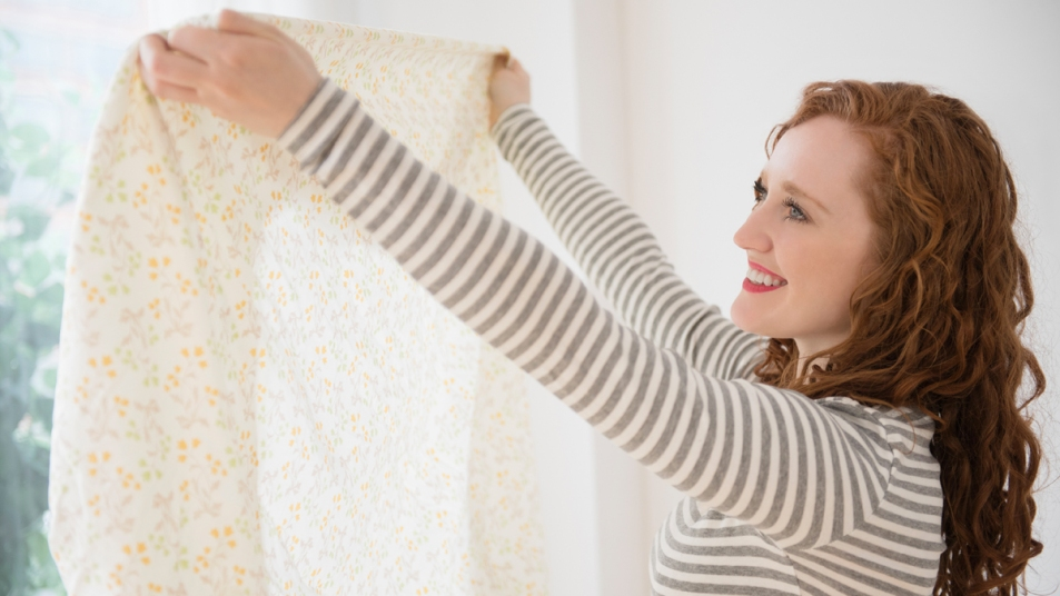 Woman holding up a fitted sheet