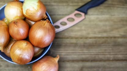 Bowl of onions with knife behind them