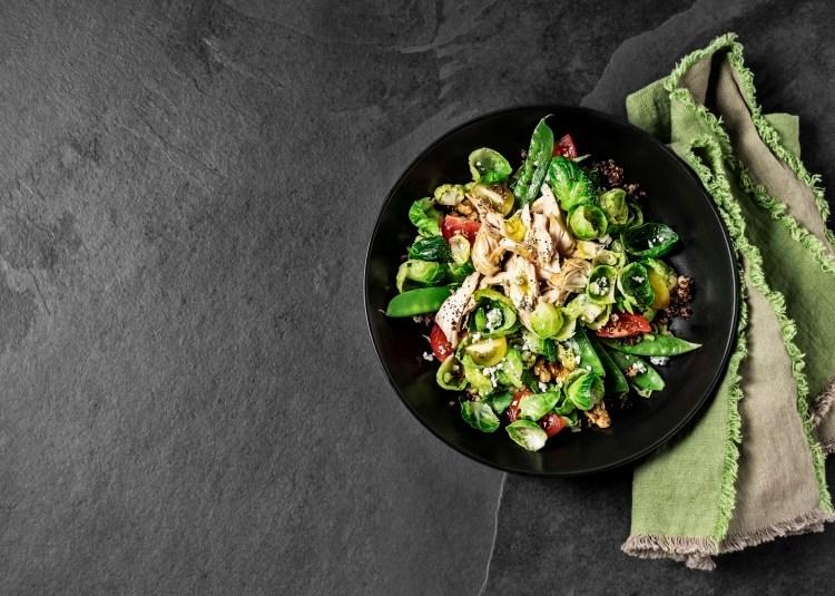 Fresh salad with chicken breast on black background