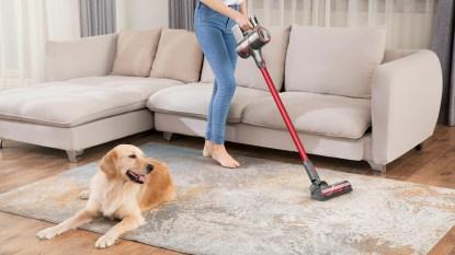 woman vacuuming with Roborock H6 Adapt Cordless Stick Vacuum